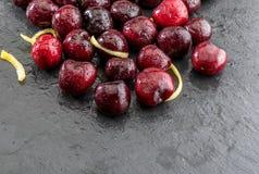 Kostbare rote und neue Kirschhalbe liter, frisch und roh auf einem strukturierten und geäderten schwarzen Hintergrund Mit zitrone stockfotografie