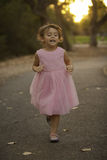 Kostbares ittle Mädchen im rosa Kleid, das bei Sonnenuntergang läuft Stockfotografie