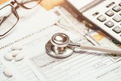 Kosten des Gesundheitswesenkonzeptes, -stethoskops und -taschenrechners auf Tabelle Lizenzfreies Stockfoto