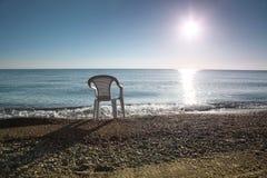 In kosten van de ochtend de aan wal witte lege plastic stoel Stock Afbeeldingen