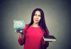 Kosten van universiteitsonderwijs Nadenkend vrouwen in evenwicht brengend spaarvarken en boek royalty-vrije stock afbeeldingen