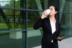 Kostium dama pije gorącego kawowego mienie komputer Fotografia Stock