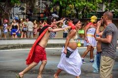Kostiumowy mąż udaje gryźć jego ciężarnej szczęśliwej żony z ogromnym plastikowym pacyfikatorem przy Carnaval 2017 z młoteczkowym zdjęcia stock