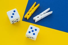Kostka do gry i clothespins na koloru żółtego tle, zakończenie zdjęcie stock