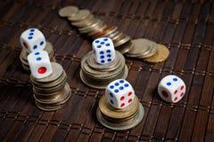 Kostka do gry i monety różni kraje na ciemnym tle zdjęcie royalty free