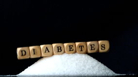 Kostka do gry literuje cukrzyce spada nad stosem cukier na czarnym tle zbiory