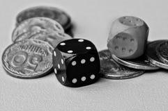 Kostka do gry na stosie monety na stole Fotografia Stock