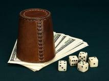 Kostka do gry, rzemienna filiżanka i dolary. Zdjęcie Royalty Free