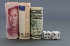 Kostka do gry umieszczający z trzy walutami fotografia stock