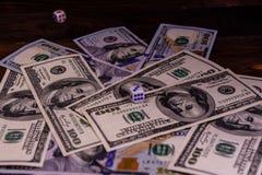 Kostka do gry w locie nad sto dolarowych rachunków Hazard conc Obraz Royalty Free
