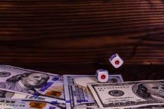 Kostka do gry w locie nad sto dolarowych rachunków Hazard conc Obrazy Royalty Free