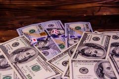 Kostka do gry w locie nad sto dolarowych rachunków Hazard conc Fotografia Stock