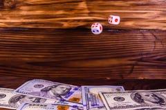 Kostka do gry w locie nad sto dolarowych rachunków Hazard conc Zdjęcia Stock