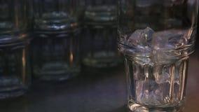 Kostka lodu spada w szkło Kelner przygotowywa świeżego napój w restauracji zbiory