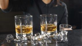 Kostka lodu spada w szkło z whisky barmanu poj?cie swobodny ruch Lód opuszcza HD zbiory