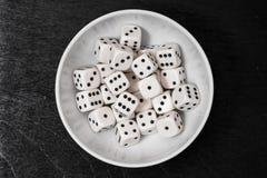 Kostki do gry w białym pucharze na czerni wsiadają zdjęcia stock