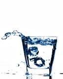 Kostki lodu bryzga w szkło, kostka lodu opuszczali w szkło woda, świeżego, zimna woda, odizolowywająca na białych, błękitnych, ca Obraz Stock