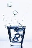 Kostki lodu bryzga w szkło, kostka lodu opuszczali w szkło woda, świeżego, zimna woda, odizolowywająca na białym błękitnym, błęki Zdjęcia Royalty Free