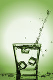 Kostki lodu bryzga w szkło, kostka lodu opuszczali w szkło woda Zdjęcie Stock