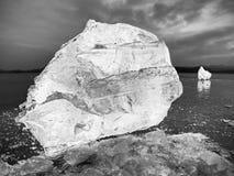 Kostki lodu na ciemnej odbijającej ziemi Jarzyć się kawałki siekający płatki śniegu i lód Obraz Royalty Free