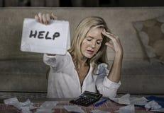 Kostnader för hemhjälp för bekymrad och stressad Caucasian notepad för 40-talkvinna hållande beräknande och skattbetalningar i bu Royaltyfria Bilder