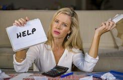 Kostnader för hemhjälp för bekymrad och stressad Caucasian notepad för 40-talkvinna hållande beräknande och skattbetalningar i bu Fotografering för Bildbyråer