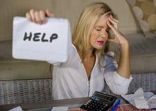 Kostnader för hemhjälp för bekymrad och stressad Caucasian notepad för 40-talkvinna hållande beräknande och skattbetalningar i bu Arkivbild