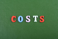 Kostnader uttrycker på grön bakgrund som komponeras från träbokstäver för färgrikt abc-alfabetkvarter, kopieringsutrymme för anno Royaltyfri Bild