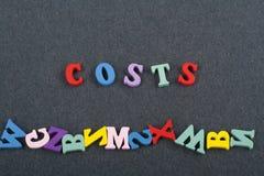 Kostnader uttrycker på svart brädebakgrund som komponeras från träbokstäver för färgrikt abc-alfabetkvarter, kopieringsutrymme fö Fotografering för Bildbyråer