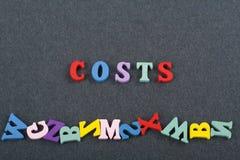 Kostnader uttrycker på svart brädebakgrund som komponeras från träbokstäver för färgrikt abc-alfabetkvarter, kopieringsutrymme fö Royaltyfri Bild