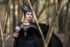 Kostuumdrama Prachtige en Magische Maleficent Vrouw met Hoornen die in de Lente Leeg Bos met Oplichter stellen royalty-vrije stock afbeeldingen