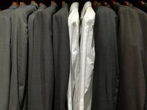 Kostuums voor mensen in een winkel en twee witte overhemden stock foto's