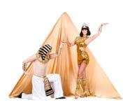 Dansare som kläs som egyptier som poserar mot pyramiden royaltyfri fotografi