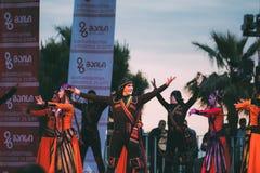 Kostymerar iklädda traditionella folk för folk dans under cen Royaltyfria Bilder