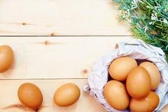 Kosz Brown jajka na drewnianym tle, odgórny widok od above z kopii przestrzenią Zdjęcie Stock