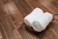 Kosz czyści biali ręczniki na drewnianym stole Zdjęcia Stock