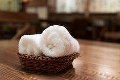 Kosz czyści biali ręczniki na drewnianym stole w restauraci Obraz Stock