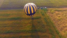 Kosz gorące powietrze balonu pozycja na polu, ludzie skacze od gondoli, koniec zbiory
