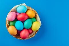 Kosz kolorowi Easter jajka na błękitnym tle Obraz Stock