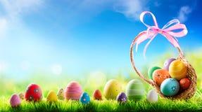 Kosz Wielkanocni jajka ręcznie malowany Z mimozami Na trawie Fotografia Stock