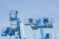 Kosz wieloskładnikowi forklifts jest stary błękit na niebieskiego nieba backgro Zdjęcie Stock