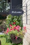 Kosz z czerwień kwiatami i znak powitalny na mieścimy ścianę Obraz Royalty Free