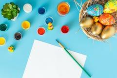 Kosz z handmade Wielkanocnymi jajkami obok multicolor muśnięcia na białej księdze na błękitnym bacground i farb fotografia stock
