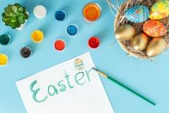 Kosz z handmade Wielkanocnymi jajkami obok multicolor mu?ni?cia na bia?ej ksi?dze na b??kitnym bacground i farb fotografia royalty free