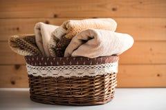 Kosz z kąpielowymi ręcznikami na drewnianym tle zdjęcie royalty free