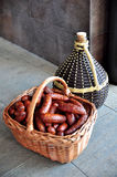 Kosz z kiełbasami i carboy wino Obraz Royalty Free