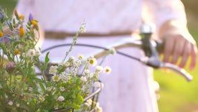 Kosz z kwiatu zakończeniem Kobieta stoi blisko jej bicyklu przy zmierzchem zbiory wideo