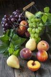 Kosz z nektarynami, brzoskwiniami, winogronem i bonkretami, Fotografia Stock