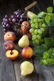 Kosz z nektarynami, brzoskwiniami, winogronem i bonkretami, Fotografia Royalty Free