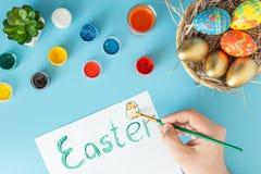 Kosz z ręcznie robiony Wielkanocnymi jajkami obok multicolor ręki z muśnięciem i farb które malują Wielkanocnego jajko na białej  zdjęcia stock